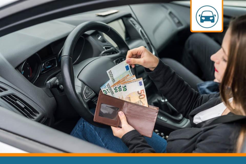 conductrice avec des euros pour payer le prix de son assurance auto